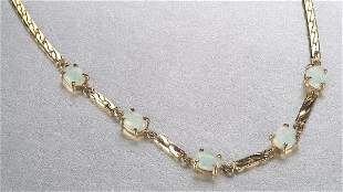 A 14K YELLOW GOLD AND OPAL NECKLACE. Fea