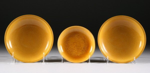 24: THREE CHINESE YELLOW GLAZED DISHES. - Two: 6 in. di