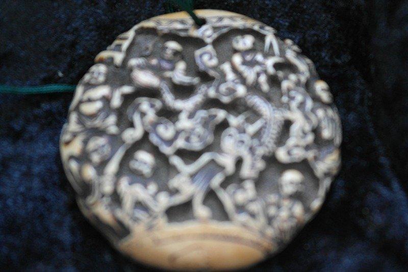 Many monks carved onto a round disc Tibetan origin