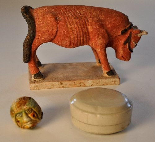 A Chinese Yuan Dynasty pottery bull on platform base Le