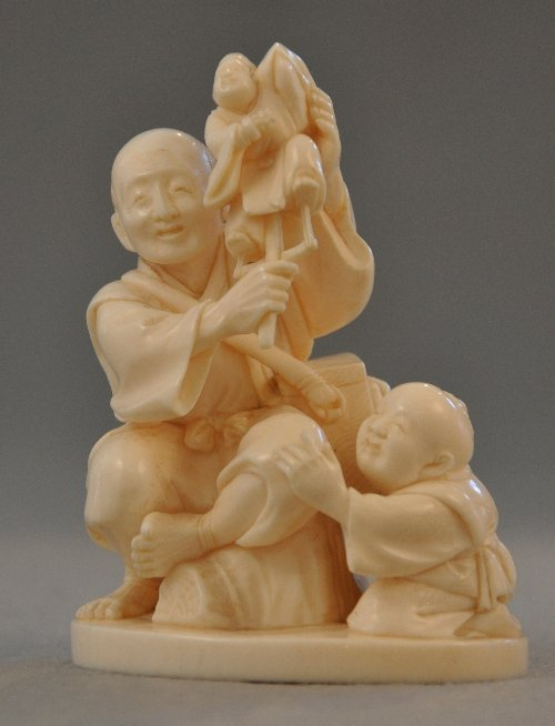A Japanese Meiji period ivory puppeteer and child