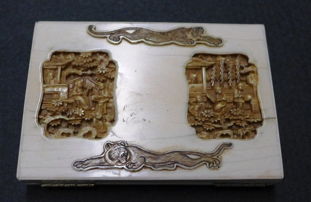 A C19th Chinese carved ivory card case with lion detail