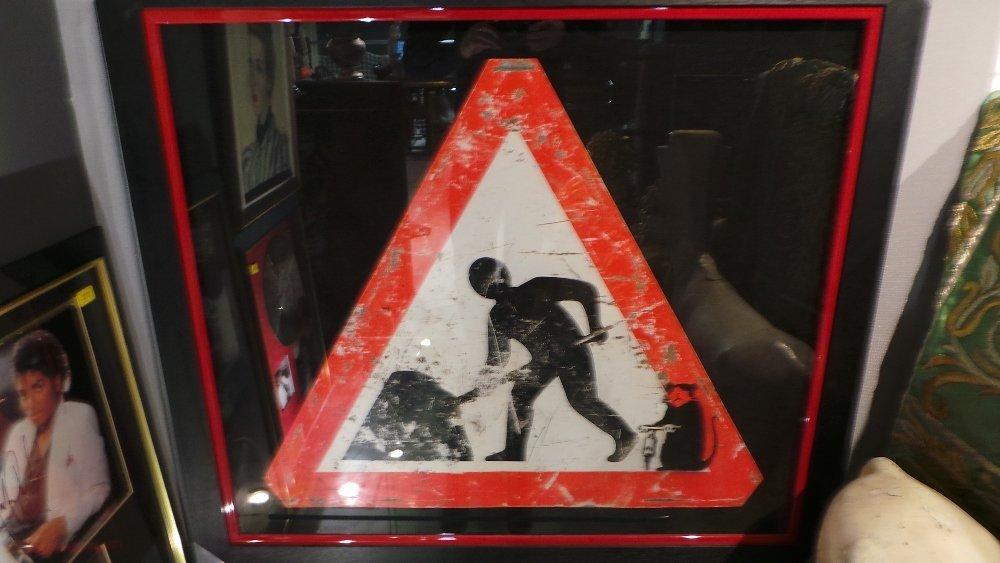 A British roadsign 'Men Working' with urban rat