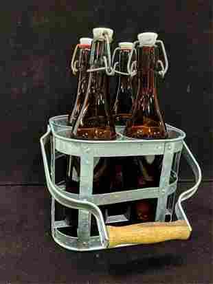 4 brown wine bottles in metal carrier
