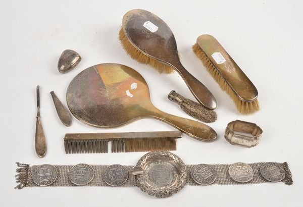 A silver coloured ashtray with a strap, set along