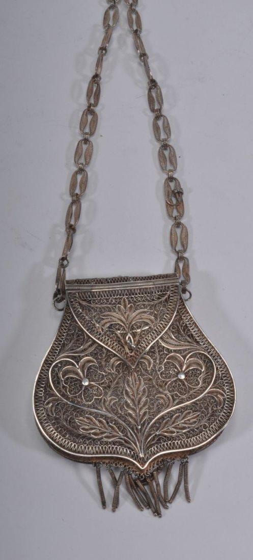 A silver coloured filigree purse, in the forum of