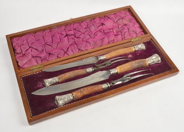 A cased four piece stag horn handled carving set w