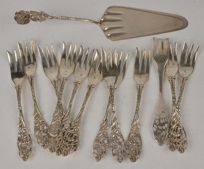 A set of twelve silver coloured cake forks with fo