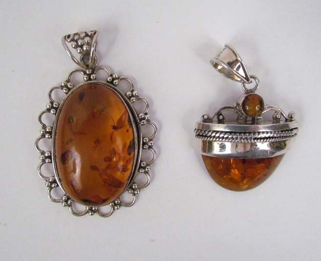 2 sterling pendants set with polished Amber cabochons