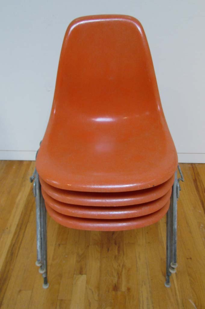 Four Eames Orange Stacking Shell Chairs