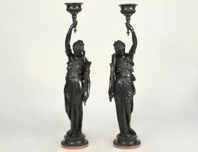 PAIR OF EBONIZED COMPOSITE STONE FIGURAL TORCHIERES
