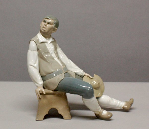 1012: Lladro porcelain figure of a seated peasant.