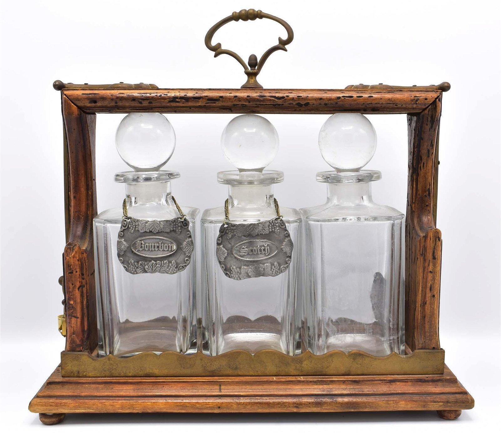 BRASS MOUNTED OAK TANTALUS & THREE GLASS DECANTERS