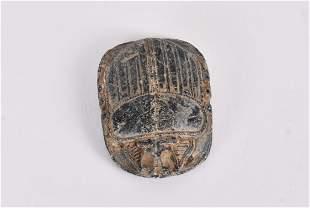 LATE PERIOD EGYPTIAN GRAYISH-BLACK STONE SCARAB