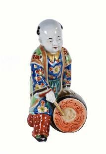 JAPANESE PORCELAIN FIGURE OF A BOY DRUMMER