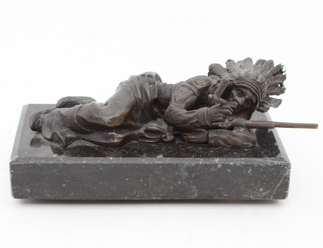 PATINATED BRONZE OF A RECLINING INDIAN CHIEF
