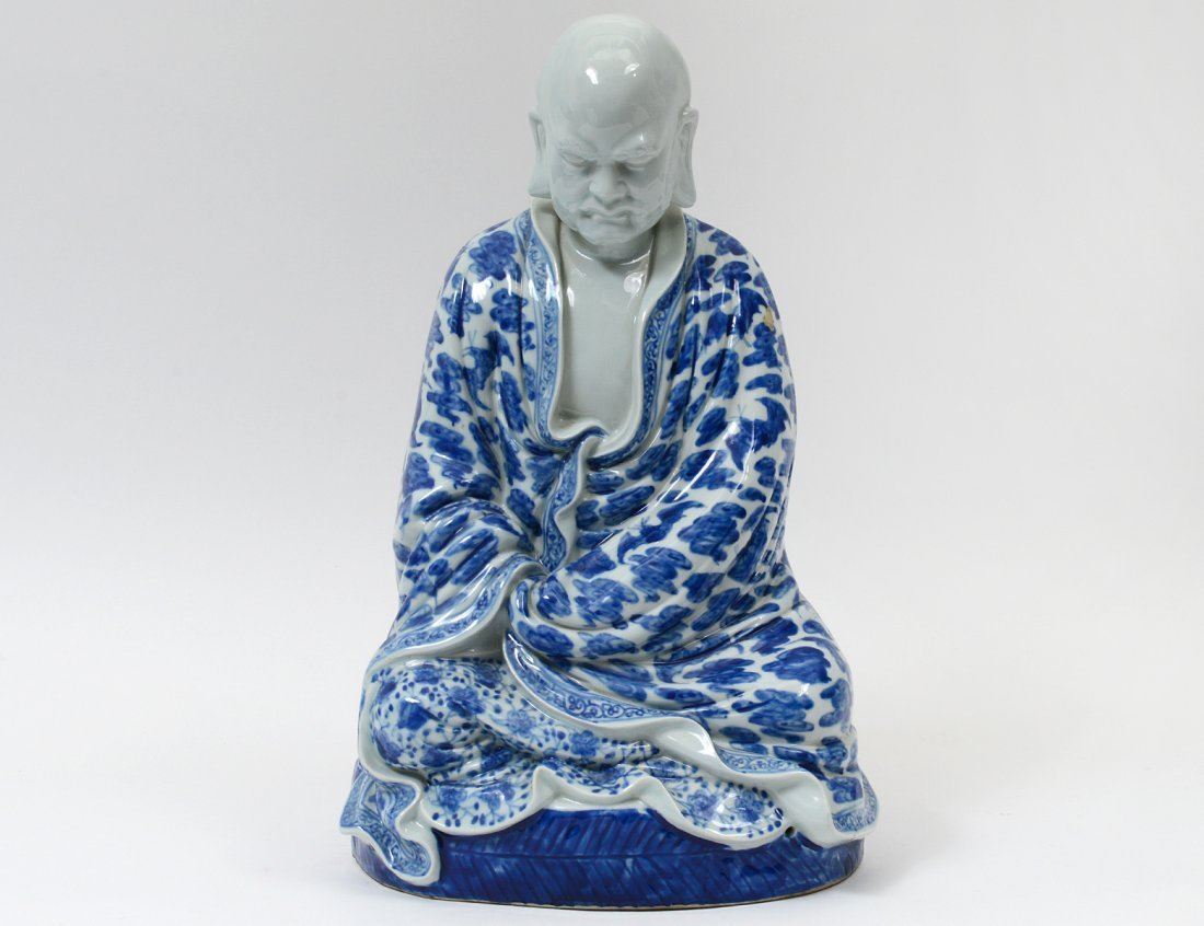 BLUE AND WHITE PORCELAIN FIGURE OF A PRAYING MONK