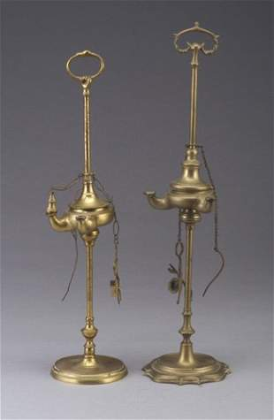 Two Roman-style brass oil lamps on tall s