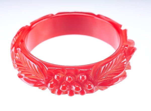 4: Red bakelite bangle with deeply-carved leaf and berr