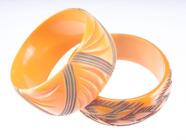 11: Two tan bakelite bangles, both with green-tinted ca
