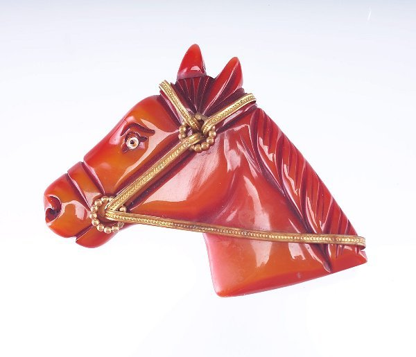 17: Bakelite horse pin with tooled brass harness, in bu