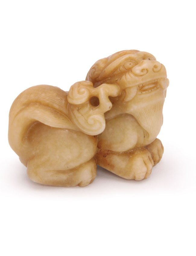 A Ming style Carved yellow jade figure of a lion dog