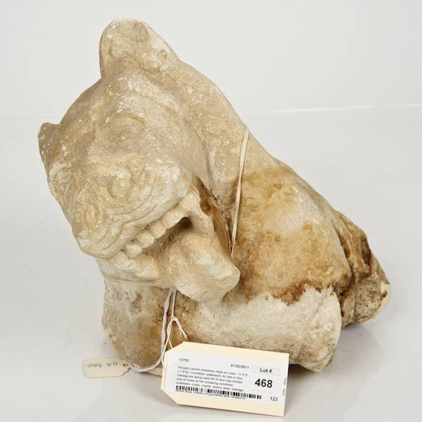 468: Ancient carved limestone head of a lion