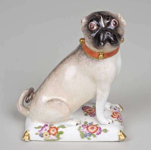 1003: Early Meissen figure of a seated Pug on cushion