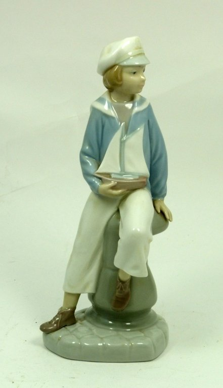LLADRO BOY SEATED ON PYLON HOLDING TOY SAIL BOAT