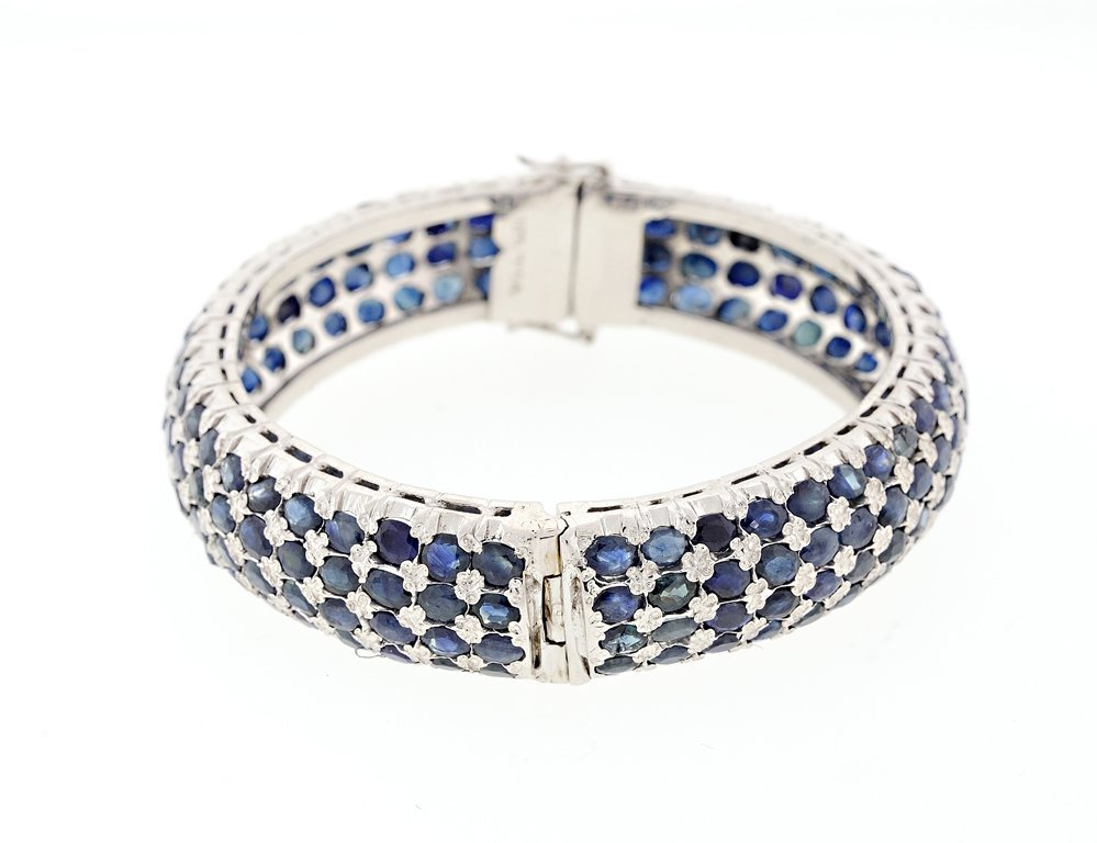 A STERLING SILVER AND BLUE SAPPHIRE BANGLE BRACELET