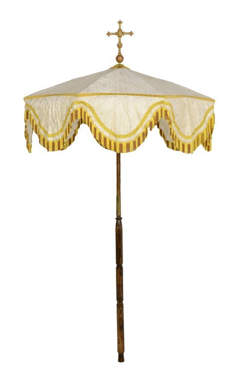 A CEREMONIAL UMBRELLA WITH A CROSS, SCALLOPED EDGE, AND