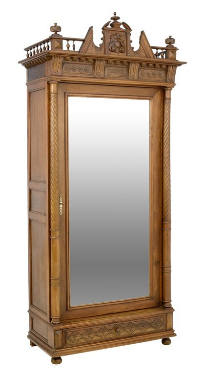 A NEOCLASSICAL STYLE MIRRORED ARMOIRE IN A WALNUT