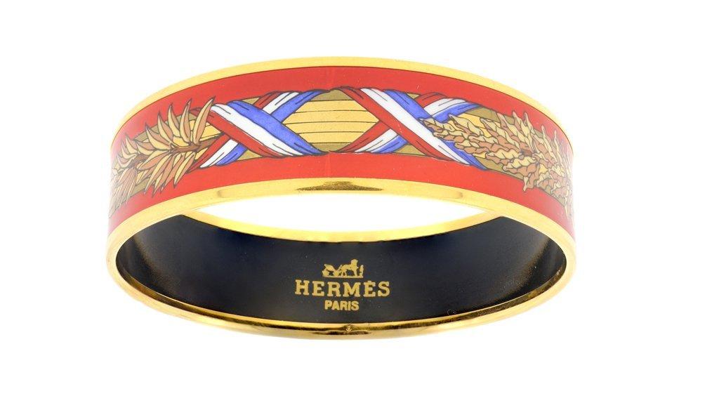 AN HERMÈS RED ENAMEL AND GOLDTONE BANGLE BRACELET