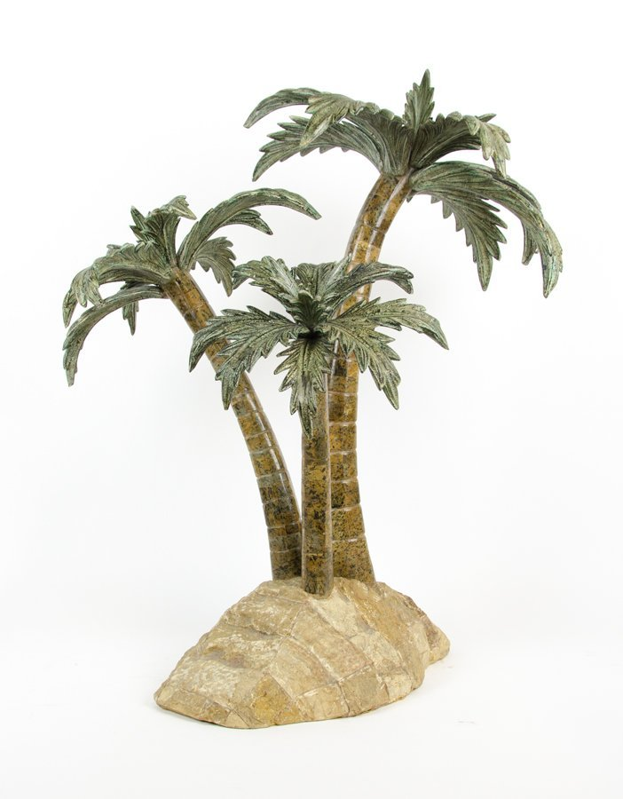 A DECORATIVE MODEL OF THREE PALM TREES ON AN ISLAND