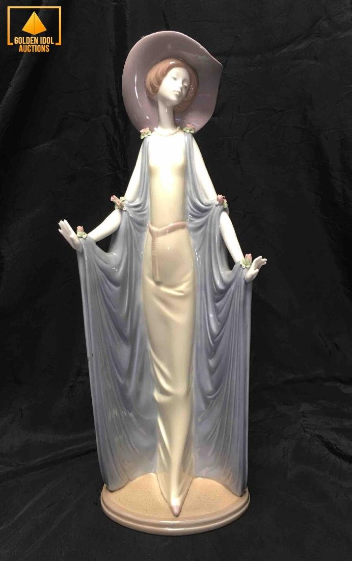 Lladro lady figurine with dress and hat.