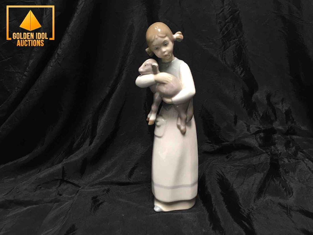Lladro little china figurine embracing a lamb.
