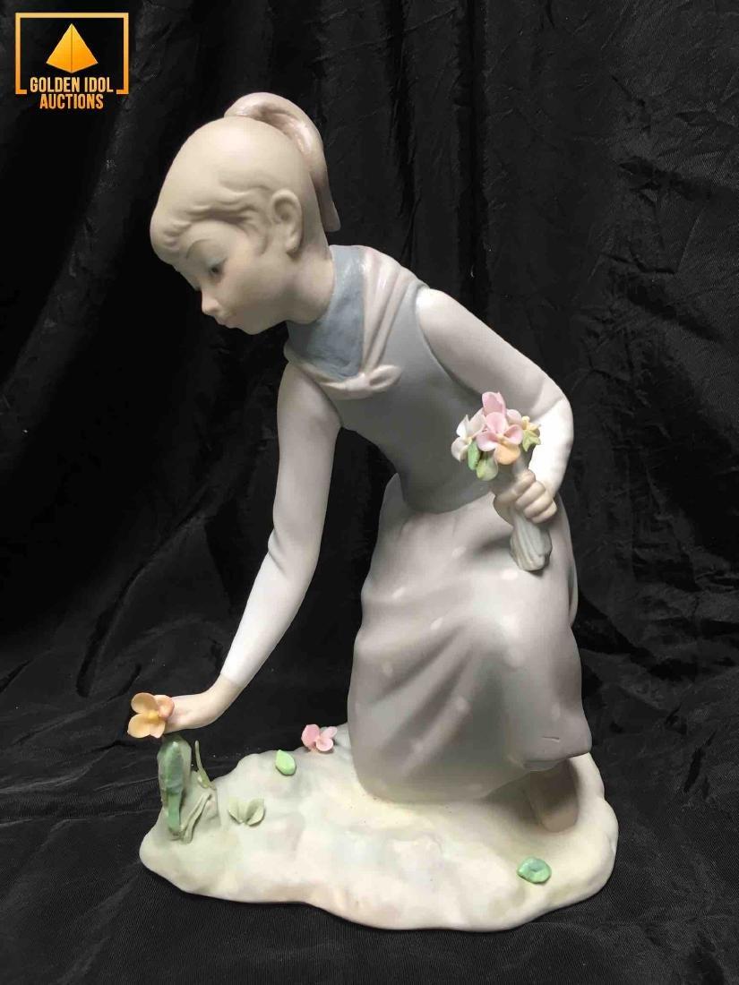 Lladro Porcelain figurine of girl picking flowers.