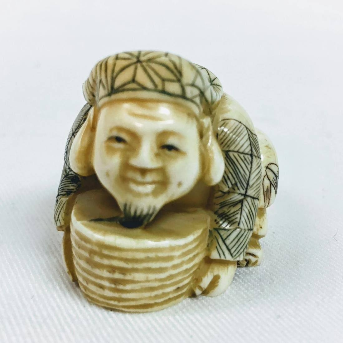 19th century Netsuke man crouching, signed