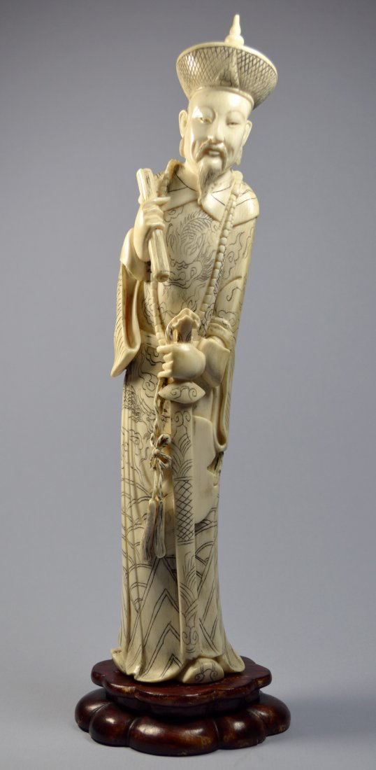 A LARGE CHINESE CARVED IVORY STATUE OF A DEITY