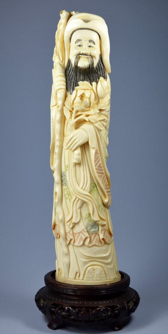 A CHINESE CARVED IVORY SCULPTURE OF A SCHOLAR