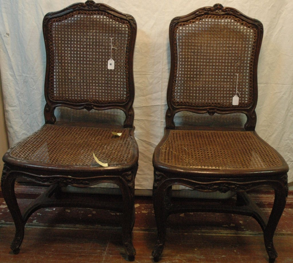 A pair of carved chairs with cane seats and backs