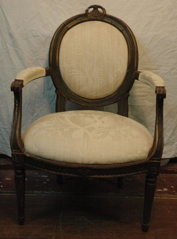 A paint decorated carved and upholstered chair