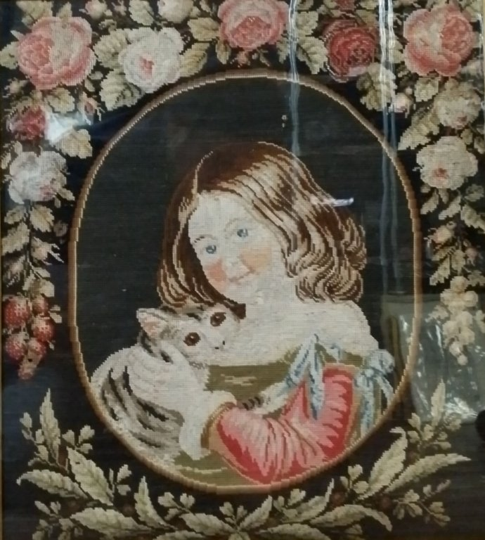 A Victorian needlepoint of a young girl with a cat