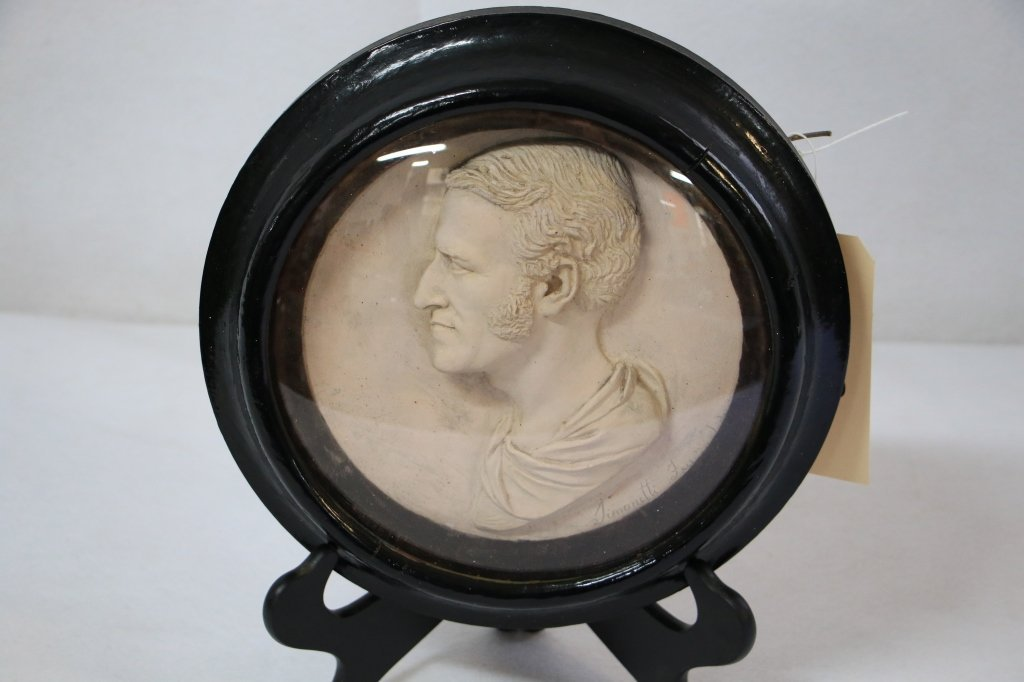 A relief plaque of a man's head in profile
