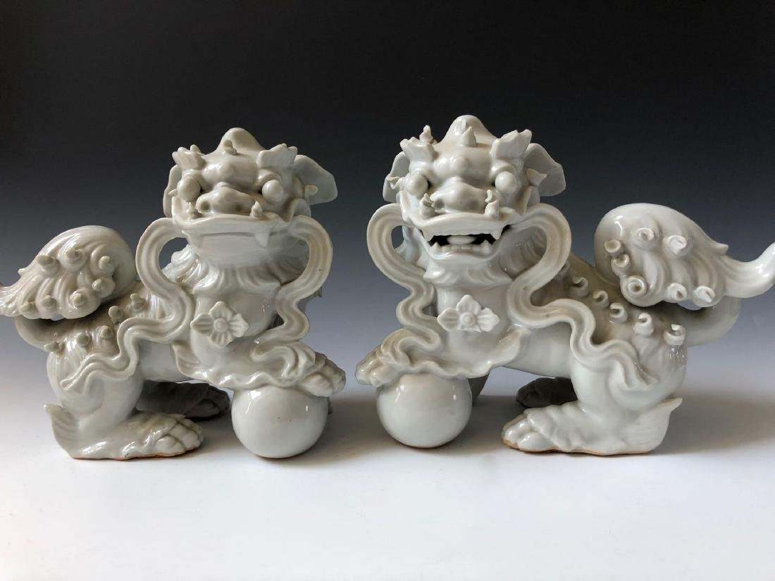 A PAIR OF CHINESE ANTIQUE WHITE GLAZED LIONS