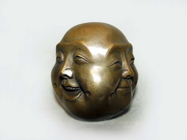 A bronze four-way buddha head, with expressions on the