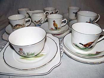 A handpainted teaset by Dulcie Vaughan, depicting count
