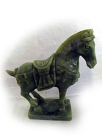 A carved green stone horse, the beast with saddle, stan