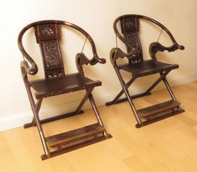 PAIR OF CARVED HORSESHOE BACK FOLDING CHAIRS