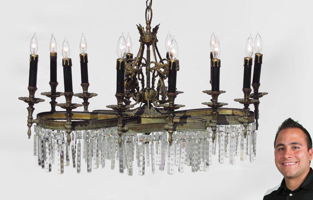 69: SERPENTINE BRONZE AND CRYSTAL 12 LIGHT CHANDELIER